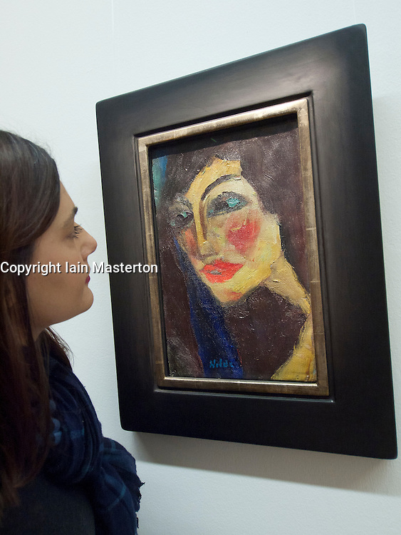 Woman looking at painting Nadja by Emil Nolde at Bonn Kunstmuseum or Art Museum in Germany