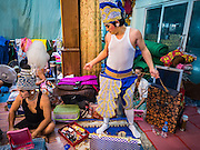 """30 JANUARY 2016 - NONTHABURI, NONTHABURI, THAILAND: A performer puts on his costume before a """"likay"""" show at Wat Bua Khwan in Nonthaburi, north of Bangkok. Likay is a form of popular folk theatre that includes exposition, singing and dancing in Thailand. It uses a combination of extravagant costumes and minimally equipped stages. Intentionally vague storylines means performances rely on actors' skills of improvisation. Like better the known Chinese Opera, which it resembles, Likay is performed mostly at temple fairs and privately sponsored events, especially in rural areas. Likay operas are televised and there is a market for bootleg likay videos and live performance of likay is becoming more rare.     PHOTO BY JACK KURTZ"""