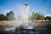 Festival goers play in the Seattle Center Fountain during the Folklife Festival in Seattle, Washington.