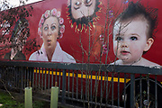Faces of a family featured in a company ad on the side of a transport truck along with roadside wasteland railings. The features of this domestic family unit has been reproduced on the lorry by a shampoo company and is seen as it is stationary at traffic lights in the east London suburb of Stratford.