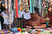 A Guatemalan woman on her stall making colourful Guatemalan textiles, in Panajachel - the largest settlement on the banks of Lake Atitlan. Lake Atitlan is seen as the most important single tourist attraction in Guatemala; and is Central Americas deepest lake. There are many villages on the banks of the lake; each with different identity and culture; the majority of the population in the region identify as indigenous Maya and many still wear traditional dress and speak Maya languages.