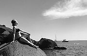 Black and white photo of a woman sunbathing on a rock at Red Beach on Santorini, Greece