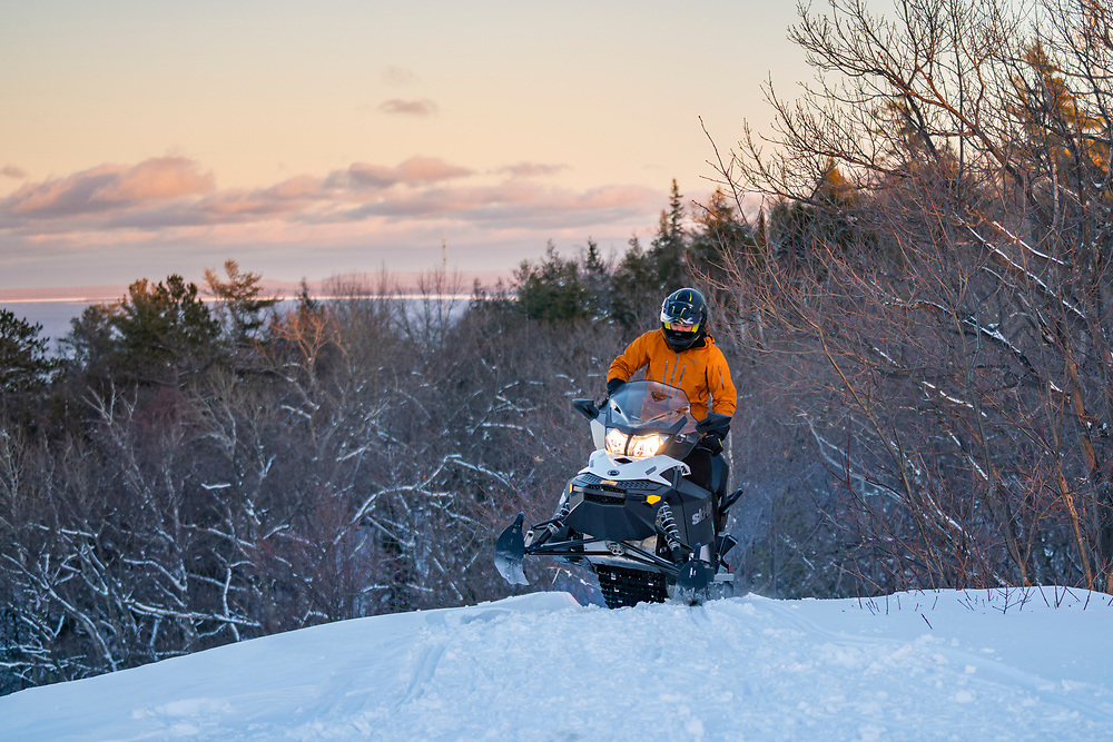 Snowmobiling the Mount Marquette Overlook road near Marquette, Michigan at sunset.