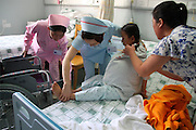 GUANGZHOU, CHINA - (CHINA OUT) <br /> <br /> 15kg Intraperitoneal Tumor Removed From 11-Year-Old Girl<br /> <br /> Han Bingbing, an 11-year-old girl from Heilongjiang, is helped onto the hospital bed for a surgery that will remove her 15kg intraperitoneal tumor ,  Han Bingbing, an 11-year-old girl from Heilongjiang, successfully received an 8-hour surgery operation to remove an intraperitoneal tumor. After 4 years, the tumor had reached a weight of 15kg and a size bigger than two footballs. As of June 18th, the tumor filled 5/6 of Bingbing's abdomen and caused her internal organs to gradually collapse. The Xukecheng Health Care Corporation raised a donation of 120 thousand RMB (19.3 thousand USD) that went towards Bingbing's surgery.<br /> ©Exclusivepix