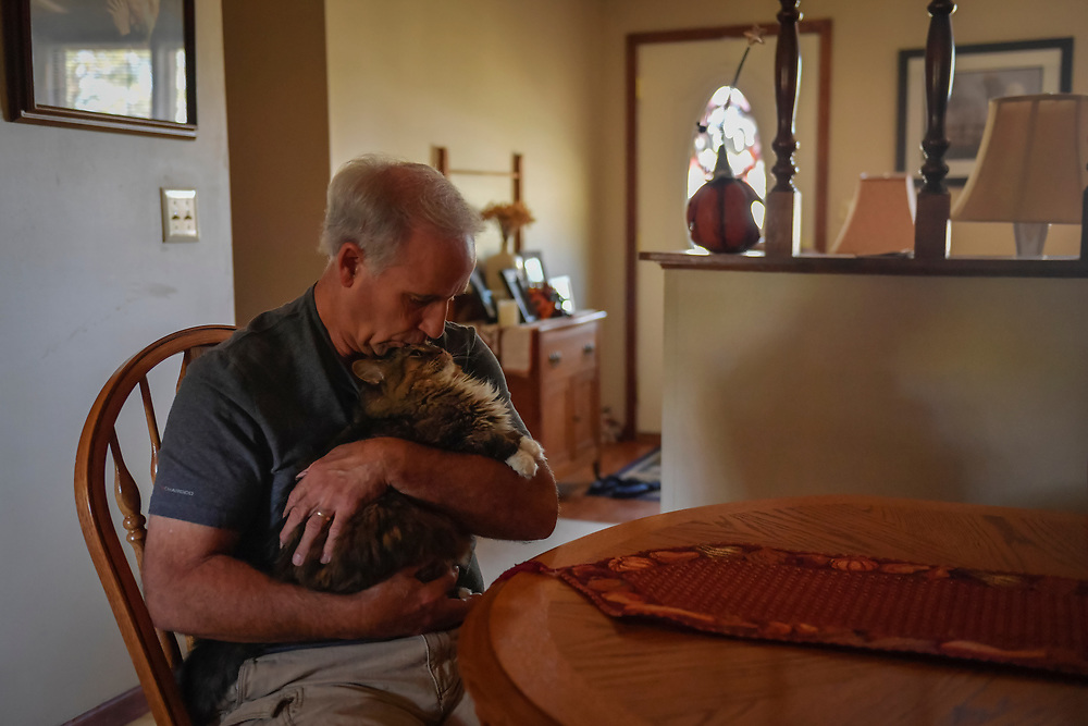 Jim Snoddy kisses his cat Roxie inside his home in Boonville, Mo.