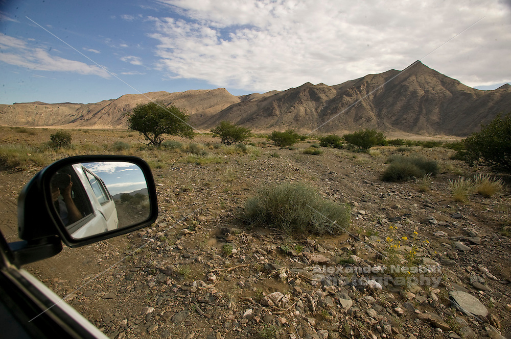 Africa, Namibia - Dry desert landsacpe near Puros viewed form the drivers seat of the typical white pickup truck.