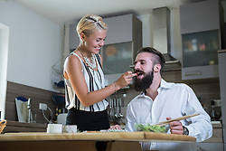 Woman feeding man in the kitchen, Bavaria, Germany