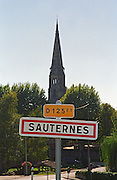 A road sign at the entrance to the village Sauternes on the road D125 E1 with the village church in the background. Sauternes, Bordeaux, Gironde Aquitaine, France, Europe