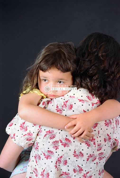 Young girl being carried by mother; looking over her shoulder,