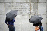 A pair of tourists shield themselves from the rain with matching umbrellas during visit to the World War II Memorial in Washington D.C.'s National Mall.