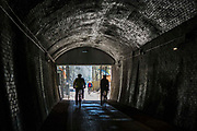 Cyclists enter the restored Devonshire Tunnel which is part of the Two Tunnels Greenway near Bath, Somerset, England, United Kingdom on 6th April 2013.  The tunnel is 407 meters long and has been restored so it is accessible by foot, cycle or wheelchair and well light throughout.  The tunnel was previously part of a main railway line, the walls are blackened with a thick crust of soot from engine exhaust, while a strip in the roof is blasted clean by that same exhaust.  The tunnel is stone-lined throughout and on a curved and falling 1:50 gradient.  The tunnel is part of a 13-mile route and was restored by Sustrans in partnership with Bath and North East Somerset Council.  The opening of the route was attended by hundreds of cyclists and pedestrians to celebrate the new access to beautiful Somerset country-side.