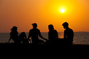 Young Indians sit on seawall at sunset at Nariman Point, Mumbai, formerly Bombay, India