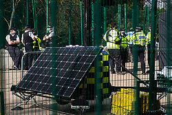 Denham, UK. 22nd March, 2021. Metropolitan Police and Thames Valley Police officers facilitate a large security operation by bailiffs from the National Eviction Team (NET) to dismantle a makeshift tower occupied by activists opposed to the HS2 high-speed rail link who were seeking to delay electricity pylon relocation works by Babcock in Denham Country Park.
