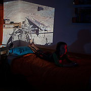 Oliver playing Xbox with a slide of the silver mines in Potosi projected onto his bedroom walls.