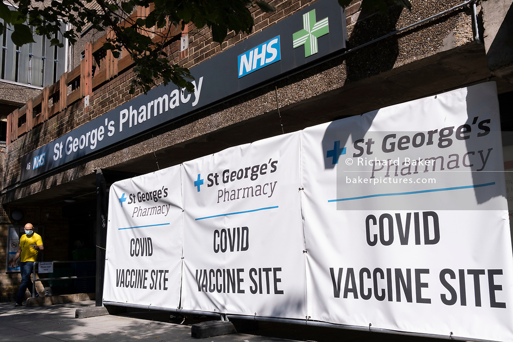 Days before the UK government's widespread re-opening of Covid pandamic restrictions (Monday 19th July aka Freedom Day), the number of daily infections has risen to 50,000, and St George's NHS Pharmacy at Elephant And castle displays its banners to encourage those elegible to have their vaccinations, on 16th July 2021, in London, England.