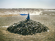 A Kata (a blessed scarf) attached to the pole of an Ovoo (shamanistic shrine) flies in the gale of the Gobi desert. <br /> Travels in the Gobi desert region.
