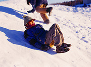 Kids playing on small hill during March in the village of Nikolai, Alaska.