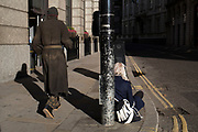 A homeless man walks past a girl who is counting how many people pass in the street. She is sitting on the ground gathering her statistics as the man in ragged and stained old clothes passes in an empty street in the City of London. UK.
