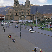 Churches, cathedrals, vendors and tourists surround a central square in Cuzco, Peru.