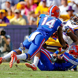 Oct 12, 2013; Baton Rouge, LA, USA; Florida Gators defensive back Jaylen Watkins (14) and defensive back Vernon Hargreaves III (1) tackle LSU Tigers wide receiver Jarvis Landry (80) during the first half of a game at Tiger Stadium. Mandatory Credit: Derick E. Hingle-USA TODAY Sports