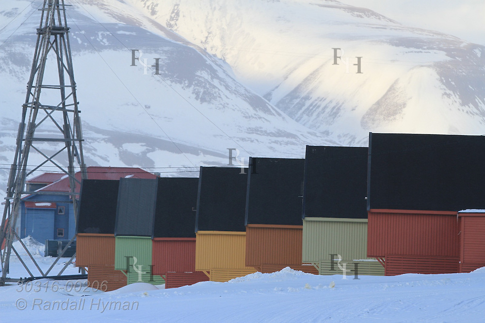 Colorful homes sit in a row beneath snowy mountains that surround town of Longyearbyen in April; Svalbard, Norway.