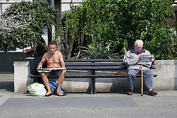 © licensed to London News Pictures. London, UK 22/05/2012. A topless and a man in a coat reading newspapers in Marble Arch today as the sunshine and hot weather comes to London (22/05/12). Photo credit: Tolga Akmen/LNP