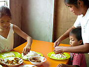 Imelda Esgana, fish vendor eating lunch at home with her two youngest children, Talisay, Bantayan Island, The Philippines. Every morning at 7 am Imelda meets the fishermen as they return from the sea with their catch. After sorting and weighing,  Imelda sells the fish locally by going house to house. Imelda and her family eat whatever is left over from her sales round. On November 6 2013 Typhoon Haiyan hit the Philippines and was one of the most powerful storms to ever make landfall.  Three-quarters of the island's population of about 136,000 depend on fishing as their main source of income. Thousands lost their boats and equipment in the storm. Oxfam is working to support the immediate and long-term needs of affected communities on Bantayan Island.