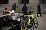 A person lies on a bench reading an Evening Standard newspaper carrying a headline about the Guinness trial, on 27th May 1991, in the City of London, England. The Guinness share-trading fraud was a major business scandal of the 1980s. It involved the manipulation of the London stock market to inflate the price of Guinness shares to thereby assist Guinness's £4 billion takeover bid for the Scottish drinks company Distillers. In May 1991, Saunders and his co-accused appealed against their convictions.