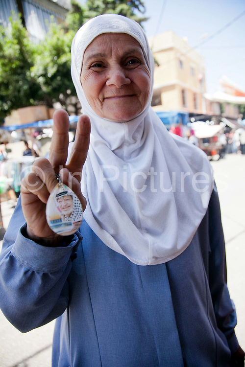 An elderly woman hold up a key ring with the image of the late PLO leader Yassir Arafat printed on. To many Palestinians Arafat is still their leader and hero in spite of his many mistakes made in the past and in spite of that he has been dead for several years.