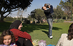 Israeli soccer star Abbas Suan,holds his son Mohammad, 2, during a family outing to the park, Ramat Gan, Israel, Jan. 31, 2006. Suan's wife Safah and daughter Mabsam, 4, are on the right. Suan, an Israeli-Arab, still faces criticism and racism resulting from the unsettled conflict between the Israelis and Palestinians.