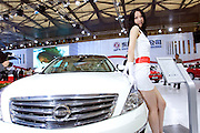 A model poses for photographs on a Dongfeng Nissan car during Shanghai Motor Show, in Shanghai, China, on April 20, 2009. Shanghai auto show opened Monday for the press and will be open April 24-28 for the public. China is the only major auto market still growing despite the global economic slowdown. U.S. and global auto makers see China as the place where they can find the sales they desperately lack in their home market. Chinese automakers see the opportunity to assess themselves as major players in the world market. Photo by Lucas Schifres/Pictobank