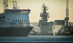 © Licensed to London News Pictures. 1/12/2016. Portsmouth, UK. A ferry (L) passes the former Royal Navy aircraft carrier HMS Illustrious as tugs move her from Portsmouth Naval Base out into the harbour ahead of her final voyage to a scrap yard.  Illustrious, the last of the Invincible Class carriers, has been sold to the Leyal Ship Recycling and Dismantling company in Aliaga, Turkey - the same yard that dismantled her sister ships Ark Royal and Invincible. Photo credit: Peter Macdiarmid/LNP
