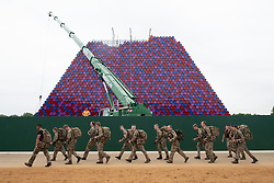© Licensed to London News Pictures. 07/06/2018. London, UK. A group of army personnel march past the CHRISTO and JEANNE-CLAUDE 'The Mastaba' sculpture in Hyde Park's Serpentine Lake. The artwork is made from 7,506 specially fabricated multi-coloured barrels and will float in the middle of the lake.Photo credit: Ray Tang/LNP