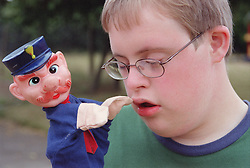 Portrait of boy with Downs Syndrome playing with hand puppet,