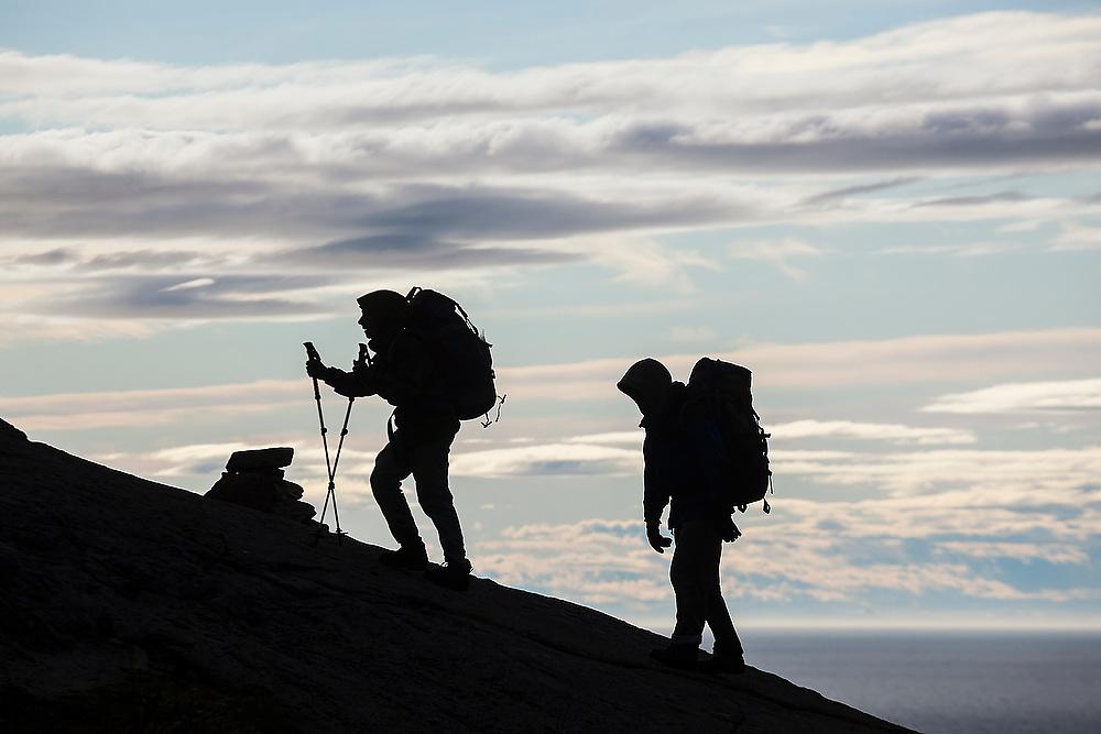 Liana (left) and Parmenter Welty hike up a ridge above Sorvagen, Moskenesoya, Lofoten Islands, Norway.