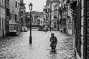 Venice, Italy. 29 October, 2018.  A man walks into the high tide along a canal in Cannaregio district on October 29, 2018, in Venice, Italy. This is a selection of pictures of different areas of Venice that the press has not covered, were resident live and every year they have to struggle with the high tide. Due to the exceptional level of the 'acqua alta' or 'High Tide' that reached 156 cm today, Venetian schools and hospitals were closed by the authorities, and citizens were advised against leaving their homes. This level of High Tide has been reached in 1979. © Simone Padovani / Awakening / Alamy Live News