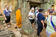 19 MARCH 2006 - SIEM REAP, SIEM REAP, CAMBODIA: A Buddhist monk walks among tourists in the Angkor Wat complex near Siem Reap, Cambodia. More than one million tourists are expected to visit Angkor in 2006 and it is the largest tourist attraction in Cambodia. It is also still one of the most important centers of Buddhism in Cambodia. PHOTO BY JACK KURTZ