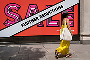 A shopper walks past Selfridges whose Summer Sale is advertised in their window banners on Oxford Street in the West End on Covid 'Freedom Day'. This date is what Prime Minister Boris Johnson's UK government has set as the end of strict Covid pandemic social distancing conditions with the end of mandatory face coverings in shops and public transport, on 19th July 2021, in London, England.
