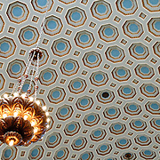 Chandelier against patterned ceiling in the Lancaster Quilt and Textile Museum in the historic downtown section of Lancaster, Pennsylvania. The museum specializes in Amish quilts from the nearby region. Lancaster is the hub of Pennsylvania Dutch Country (also known as Amish community). The building housing the museum was formerly an historic bank and it retains the large bank vault, which now contains a