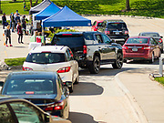 09 MAY 2020 - DES MOINES, IOWA: A drive through farmers' market in Des Moines. The Governor allowed farmers' markets across the state to reopen last weekend, but limited them to selling just food stuffs. They are not allowed to have entertainment or sell non-food items. Most farmers' markets in Iowa are taking a wait and see approach to reopening. The Downtown Farmers Market in Des Moines announced they won't reopen until July. Three vendors set up their own drive through farmers' market in the parking lot of Des Moines theatre Saturday. Hundreds of people got in line to buy fresh produce and artisan cheese. More than 11,670 people have tested positive for COVID-19 in Iowa and more than 250 have died from the disease.          PHOTO BY JACK KURTZ