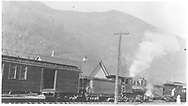 """Rear engineer's-side view of an RGS C-16 ready to depart Telluride northbound with the #6 passenger train.  Another passenger train is ahead where two ladies are exchanging greetings.<br /> RGS  Telluride, CO  Taken by Virden, Walter - ca. 1920-1929<br /> In book """"Rio Grande Southern, The: An Ultimate Pictorial Study"""" page 87<br /> Also at RD131-049 and RD155-096.  Also in """"RGS Story Vol. II"""", p. 93.<br /> Thanks to Don Bergman for additional information."""