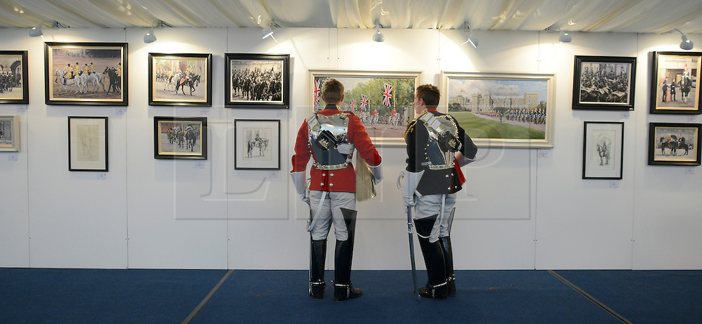 © Licensed to London News Pictures. 20/04/2012. London, UK . Two soldiers look at the paintings. A Preview of the Household Cavalrys 'The Best of British' art exhibition. Soldiers walk around the artwork as they prepare to mount duties at Horse Guards Parade. The Queen's Life Guard are inspected before they depart the Barracks for the daily Guard change at 1100. The exhibition runs between 23 - 26 April. Hyde Park Barracks, Ceremonial Gate, South Carriage Drive, London, SW7 1SE. Photo credit : Stephen Simpson/LNP