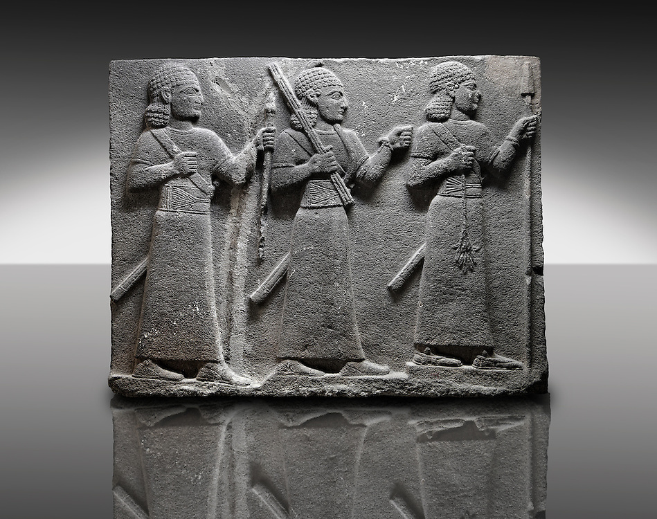 Picture & image of a Neo-Hittite orthostat of 3 warriors from the legend of Gilgamesh from Karkamis,, Turkey. Museum of Anatolian Civilisations, Ankara. The warrior on the far left holds a spear in one hand and the branch of a tree in the other. The middle warrior has a clenched fist an carries an impliment over his shoulder. The warrior on the far right carries a saff. All 3 are wearing swords.  3