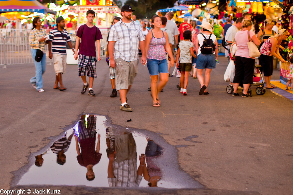 """01 SEPTEMBER 2011 - ST. PAUL, MN:  People walk through the midway at the Minnesota State Fair. The Minnesota State Fair is one of the largest state fairs in the United States. It's called """"the Great Minnesota Get Together"""" and includes numerous agricultural exhibits, a vast midway with rides and games, horse shows and rodeos. Nearly two million people a year visit the fair, which is located in St. Paul.   PHOTO BY JACK KURTZ"""