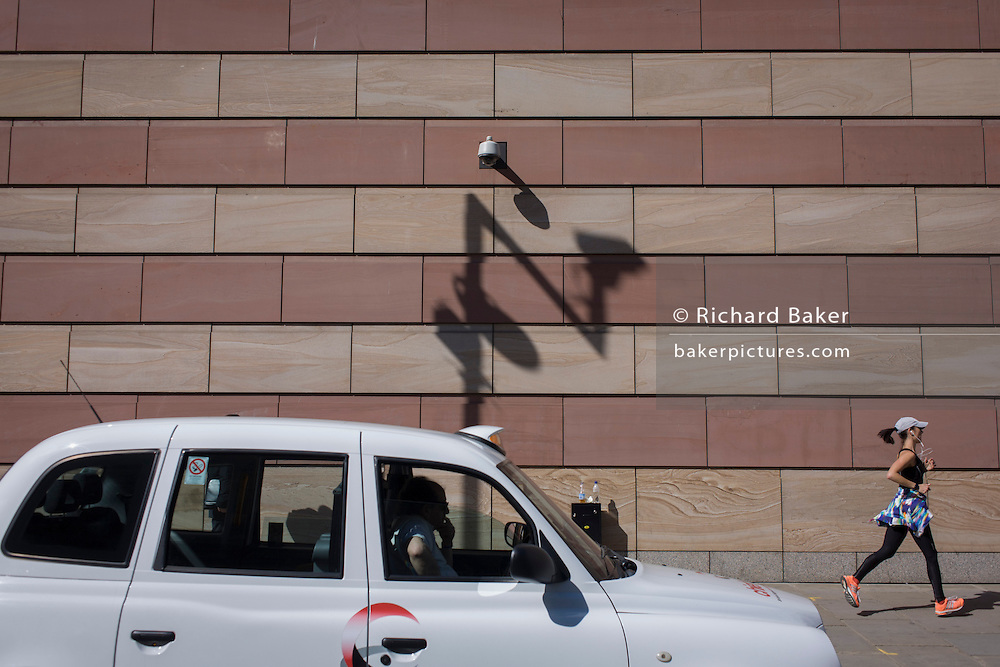 A lady jogger is watched by a taxi driver below a CCTV camera with the shadow of a traffic camera on the wall of a modern office building in the City of London, the capital's financial district.