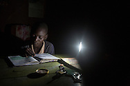 Levis Opiyo, 14, does his homework with the help of a solar lamp his older brother Felix purchased for him in Miranga Village, Kenya. Felix  was left orphaned  and in charge of 4 year old twins when he was 14 and lost both his parents to the HIV epidemic. Studying is what got him through the most difficult times. Although he did well in his exams that qualified him to go to a good secondary school, he didn't have the money to continue his studies. He was totally lost when he came across a representative of The Children Behind project and got full funding for his school fees. The project aims to improve the quality of life for orphans, vulnerable children, and their caregivers in communities with a high prevalence of HIV. The project was started in 2002 and has been funded solely through CRS private donations. It currently supports over 13,000 people. Felix is now a university student pursuing a degree in statistics. He works at St. Paul's when he's on vacation and uses his wages to pay for his studies. He regularly checks in on Levis and makes sure he is doing well in school. (CONSENT FORMS SIGNED)