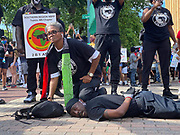 6/6/2020 Jackson MS. <br /> Pictured is Barbara Walker with her knee on the neck of National Black Panther Party Kelvin Bradfield out side the Governor Mansion after a peaceful protest by Black Lives Matter, organized by 18yr old student Maisie Brown. Bradfield chanted ''I can't breathe '' as the crown chanted _check his pulse.''as Walker held her knee on his neck in the 90 degree heat. Photo© Suzi Altman..Student Maisie Brown 18yrs old from Jackson organized a peaceful protest outside the Governors Mansion. She said there voices would be heard and her face would be seen- change is coming. The protest was in honor of George Floyd and in support of ending systematic racism and to end police brutality in Mississippi and America. The National Black Panthers Party from Tupelo Mississippi showed up outside the Governors mansion in the shadow of the State Capitol to protest police brutality. The National Black Panthers Party was their to show their support for change in Mississippi, to end systemic racism and police brutality. Protests have broken out around the world in solidarity to end white supremacy and police brutality. The Panthers showed up at the end of a peaceful protest organized by 18yr old student Maisie Brown. The brutal murder of African American George Floyd by the knee and hands of 4 former Minneapolis Minnesota police officers has sparked a cry for justice and reform around the world. Photo copyright © Suzi Altman<br /> Student Maisie Brown 18yrs old from Jackson organized a peaceful protest outside the Governors Mansion. She said there voices would be heard and her face would be seen- change is coming. The protest was in honor of George Floyd, another Black man killed by the knees and hands of 4 former Minneapolis Minnesota police officers. The protestors are demanding an end to police brutality  and systematic racism among other issues in Mississippi and America. Protests have broken out around the world in solidarity to end white supremacy and police brutal