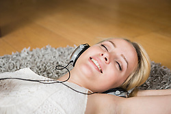 Beautiful young woman listening to music and relaxing on floor, Munich,Bavaria, Germany