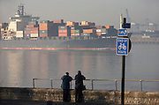 """The cargo ship """"CMA CGM Turkey"""" eases past two elderly shipping spotters who log its details on the River Thames"""