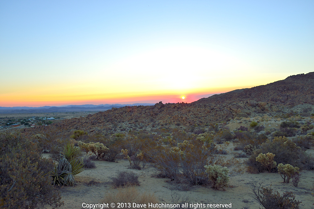 USA: California: San Bernadino County: Joshua Tree: A colorful sunrise mixes red, orange and yellow with the blue sky over the desert valley.